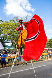 Carnival on stilts. Stilt walker up high at the Junior Parade of the Bands shows off the country's colors of red white and black during Carnival celebrations in Royalty Free Stock Photo