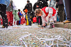Carnival street parade. Moncalieri, TURIN - FEBRUARY 21: Child takes from the road confetti during the traditional carnival street parade. February 21, 2010 in Royalty Free Stock Photography