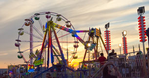 Carnival Sunset. The sun setting behind a backlit section of amusement rides at the Wisconsin State Fair Stock Photos