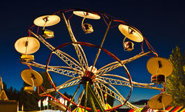 Carnival Sunset Umbrella Ride. Many carnivals operate after sunset with lots of lights Stock Photo