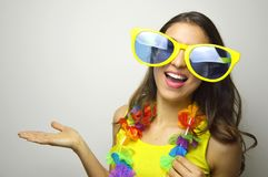 Carnival time. Young woman with big funny sunglasses and carnival garland smile at camera and show your product or text. On gray background royalty free stock photography