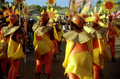 Carnival in Tobago. Women seen from the back waiting to parade for Carnival. They are wearing orange and yellow outfits. They hold sun symbols in one hand and Royalty Free Stock Photography
