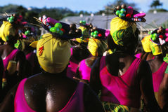 Carnival In Tobago. Women ready to start parading for Carnival. View from the back. They are wearing colorful head gears with plates that contain false fruits Stock Images