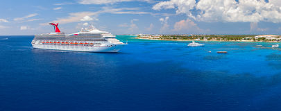 Carnival Triumph cruise ship tendered next to the tropical island. Over 3,500 guests went out to visit beautiful port. Stock Photo