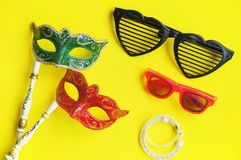Carnival venetian masks in green and red with handle, fancy glasses and glitter bracelets for photo booth isolated on vibrant yell stock image