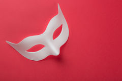 Carnival venetian white mask on red background. Royalty Free Stock Image