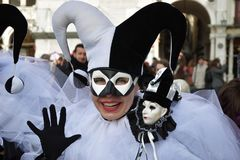 Carnival of Venice, Italy. Venice, Italy - Mar 7, 2011: Unidentified masked person in Arlecchino costume among crowd in St. Mark`s Square during the Carnival Royalty Free Stock Photography