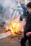CARNIVAL IN VEVCANI, MACEDONIA. VEVCANI, MACEDONIA - JANUARY 13, 2012: Dressed up participants burn a Greek flag and coffin during the symbolic funeral of Greece Stock Image