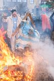 CARNIVAL IN VEVCANI, MACEDONIA. VEVCANI, MACEDONIA - JANUARY 13, 2012: Dressed up participants burn a Greek flag and coffin during the symbolic funeral of Greece Royalty Free Stock Photography