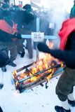 CARNIVAL IN VEVCANI, MACEDONIA. VEVCANI, MACEDONIA - JANUARY 13, 2012: Dressed up participants burn a Greek flag and coffin during the symbolic funeral of Greece Royalty Free Stock Image