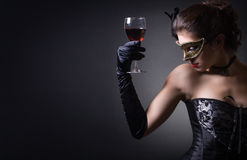 Carnival. Young woman in carnival mask and a glass of red wine stock images
