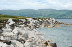 Carnlough Bay. On the coast of County Antrim, Northern Ireland, with the Glens of Antrim in the background. The white limestone boulders and pebble beaches are royalty free stock photo