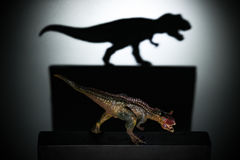 A carnotaurus casting a tyrannosaurus shadow in dark concept of strength & aspirations. A carnotaurus casting a tyrannosaurus shadow in dark concept of strength royalty free stock image