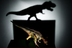 Carnotaurus casting a tyrannosaurus shadow in dark. A carnotaurus casting a tyrannosaurus shadow in dark concept of strength and aspirations Royalty Free Stock Photo