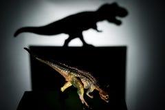 Carnotaurus som gjuter en tyrannosarieskugga i mörker Royaltyfri Foto