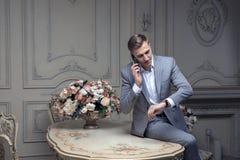 Caro giovane con un taglio di capelli in un vestito, sedentesi ad una tavola in una stanza con un interno classico lusso Bellezza immagini stock