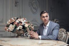 Caro homem novo com um corte de cabelo em um terno, sentando-se em uma tabela em uma sala com um interior clássico luxo Beleza ma imagens de stock