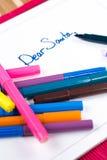 Caro sinal de Santa em um Livro Branco com as penas coloridas diferentes Imagens de Stock Royalty Free