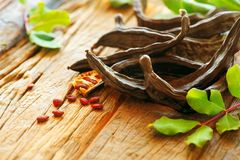 Carob. Healthy organic sweet carob pods with seeds and leaves on a wooden table. Healthy eating Stock Photo