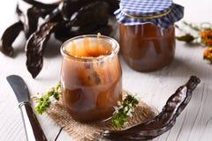 Carob jam in jar Stock Images