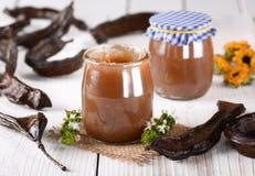Carob jam in jar. Carob jam in glass jar with fruit around Royalty Free Stock Photo