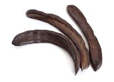 Carob pods on white background stock photo