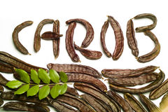 Carob written with carob pods. Carob writen with carob pods and leaves Royalty Free Stock Image
