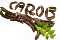 Carob written with pods Royalty Free Stock Photos