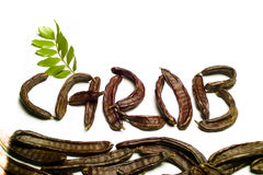 Carob written with  pods. Carob written with carob pods with green leaves on white Stock Photos