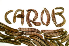 Carob written with pods. Carob writen with carob pods and leaves Royalty Free Stock Photos