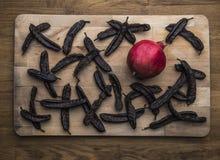 Carobs et un pommegranate d'un plat en bois image libre de droits