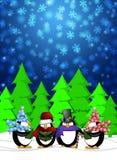 Carolers dei pinguini che cantano nella scena di nevicata di inverno Fotografia Stock