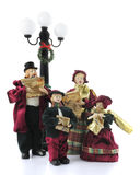 Caroling Figurines. A family of four old-fashioned caroling figurines under a wreath-adorned light post.  Isolated on white Stock Photo