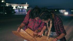 Caroneiro de duas jovens mulheres que procura pelo sentido que olha o mapa, jovens mulheres que viajam em uma estrada na cidade filme