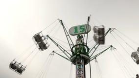 Carosello alto alto girante con la gente di volo sul fondo del cielo archivi video