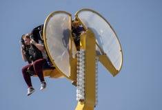Carosello felice di guida della ragazza nel parco di divertimento Fotografie Stock