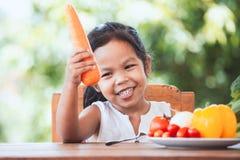 Carota asiatica della tenuta della ragazza del bambino ed imparare circa la verdura immagini stock libere da diritti