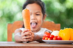 Carota asiatica della tenuta della ragazza del bambino ed imparare circa la verdura immagine stock