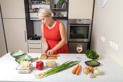Carota di taglio della giovane donna e preparare per il wok di verdure Fotografie Stock