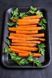 Carote arrostite con le erbe verdi in vassoio di cottura Immagini Stock Libere da Diritti