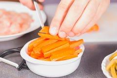 Carote di taglio del cuoco con un coltello ceramico Fotografia Stock Libera da Diritti