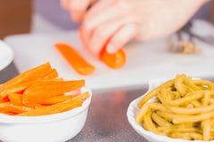 Carote di taglio del cuoco con un coltello ceramico Immagini Stock Libere da Diritti