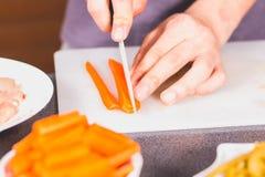 Carote di taglio del cuoco con un coltello ceramico Fotografie Stock