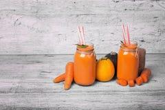 Carote e zucchini su un fondo di legno spazioso Succhi naturali delle carote, delle arance e della menta aromatica Copi lo spazio fotografie stock
