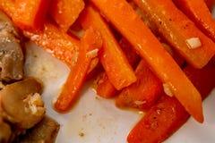 Carote, funghi ed aglio Grandi fette succose di verdure saltate su un piatto immagine stock libera da diritti