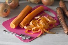 Carotte épurée se trouvant sur le conseil à côté des oignons et de la carotte photographie stock