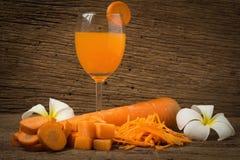 carotte coupée en tranches avec la carotte et la fleur en verre de jus sur le vieux bois Photo stock