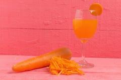 carotte coupée en tranches avec la carotte en verre de jus sur le rose en bois Photos stock