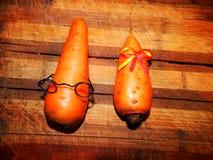 Carotte drôle de garçon de légumes dans les verres et la carotte de fille Images stock