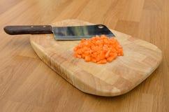 Carotte et couteau coupés de hachage sur la plaque de découpage Photographie stock libre de droits